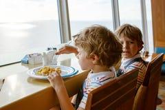 Deux garçons préscolaires d'enfants mange des pâtes se reposant dans la cantine scolaire Photos stock