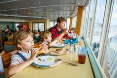 Deux garçons préscolaires et père d'enfants mangeant l'hamburger se reposant en café sur le bateau de croisière Images libres de droits
