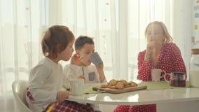 Deux garçons prenant le petit déjeuner dans la cuisine moderne Le garçon mangent le biscuit avec du lait Tableau blanc dans la cu clips vidéos
