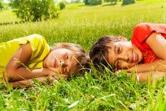 Deux garçons s'étendant sur l'herbe ensemble en parc Image stock