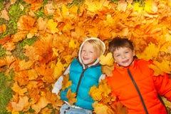 Deux garçons s'étendant sur la vue de feuilles d'automne à partir du dessus Photographie stock