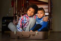 Deux garçons s'asseyant à l'intérieur de la valise Photographie stock libre de droits