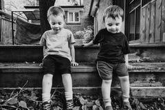 Deux garçons s'asseyant dehors ensemble photo libre de droits