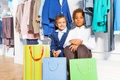 Deux garçons s'asseyant sous des cintres avec des vêtements Images stock