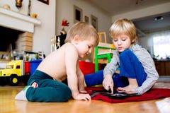 Deux garçons s'asseyant sur le plancher jouant sur le comprimé Photographie stock libre de droits