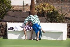 Deux garçons s'asseyant sur un banc à la piscine Images libres de droits