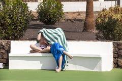 Deux garçons s'asseyant sur un banc à la piscine Image libre de droits