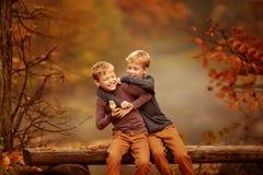 Deux garçons s'asseyant sur un banc dans les bois Images stock