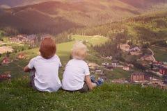 Deux garçons s'asseyant sur une colline et regardant les montagnes Dos vi Images libres de droits