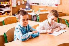 Deux garçons s'asseyent au bureau sur la leçon Photographie stock libre de droits