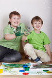 Deux garçons s'asseyent avec les visages satisfaisants et affichent des paumes Photographie stock libre de droits
