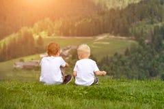 Deux garçons s'asseyent sur la colline et parler gaiement Vue arrière Photos stock