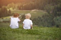 Deux garçons s'asseyent sur la colline et parler gaiement Vue arrière Images stock
