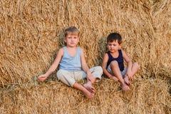 Deux garçons s'asseyent sur la grande grange image stock