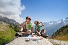 Deux garçons s'asseyent sur la grande pierre en montagnes d'été Image libre de droits