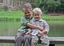 Deux garçons sur le banc en bois au lac Photos stock