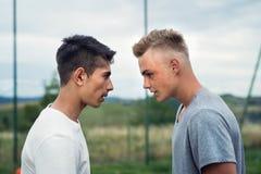 Deux garçons sur le terrain de jeu regardant l'un l'autre avec haine photo stock