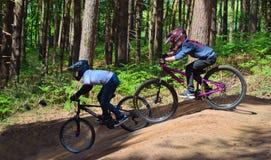 Deux garçons sur le vélo de montagne incliné courent en bois Images stock