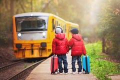 Deux garçons sur une gare ferroviaire, attendant le train avec le suitca Photos stock