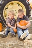 Deux garçons tenant des potirons parlant et se reposant contre le Ti de tracteur Photos stock