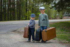 Deux garçons vont sur la route avec de grandes valises Images stock