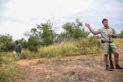 Deux gardes forestiers expliquant les dangers africains de buisson image stock