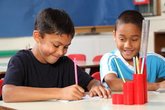 Deux garçons d'école appréciant leur apprentissage dans la classe Photos stock