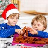 Deux garçons de petit enfant faisant des biscuits cuire au four de pain d'épice Image stock