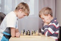 Deux garçons jouant aux échecs à la maison Photo libre de droits