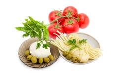 Deux genres de fromage, d'olives, de tomates et d'herbe aromatique de mozzarella Photos stock
