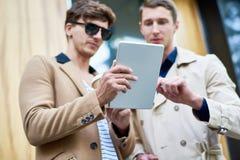 Deux gens d'affaires à l'aide de la Tablette dans la rue Photos stock