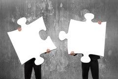 Deux gens d'affaires assemblant les puzzles denteux blancs avec le concret
