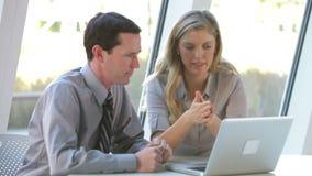 Deux gens d'affaires avec l'ordinateur portable ayant la réunion banque de vidéos