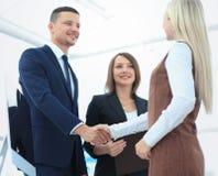 Deux gens d'affaires concluant l'accord, leur sta femelle de collègue Photographie stock