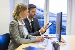 Deux gens d'affaires dans un bureau, travaillant à l'ordinateur et au comprimé images stock