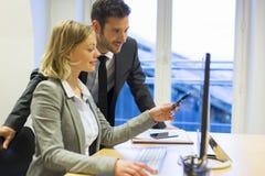 Deux gens d'affaires dans un bureau, travaillant sur l'ordinateur Images stock