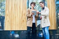 Deux gens d'affaires de sourire à l'aide de la Tablette dans la rue Photo stock