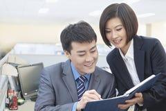 Deux gens d'affaires de sourire regardant vers le bas le bloc-notes et travaillant ensemble Photo stock