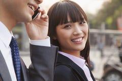 Deux gens d'affaires dehors sur la rue utilisant le téléphone dans Pékin, portrait Photos stock