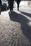 Deux gens d'affaires descendant une rue de ville, longues ombres sur la rue Photos stock