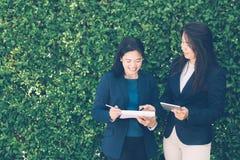 Deux gens d'affaires discutant l'information sur a Tablette-et prenant des notes comme elles fonctionnent ensemble en équipe dans photo stock