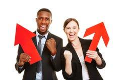 Deux gens d'affaires encourageant avec des flèches Image libre de droits