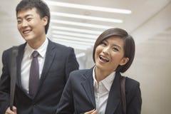 Deux gens d'affaires marchant ensemble, souriant et riant, à l'intérieur Images stock