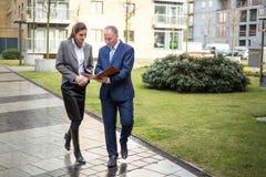 Deux gens d'affaires marchant et discutant Photographie stock libre de droits