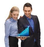 Deux gens d'affaires montrant le PC de comprimé avec le graphique Images stock