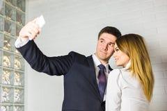 Deux gens d'affaires réussis prenant un Selfie heureux dans le bureau Photo libre de droits