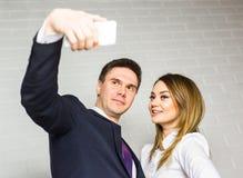 Deux gens d'affaires réussis prenant un Selfie heureux dans le bureau Images stock