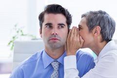 Deux gens d'affaires regardant un papier tout en travaillant au dossier Image stock