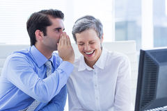 Deux gens d'affaires regardant un papier tout en travaillant sur l'ordinateur Photos stock