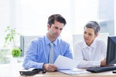 Deux gens d'affaires regardant un papier tout en travaillant sur l'ordinateur Photographie stock